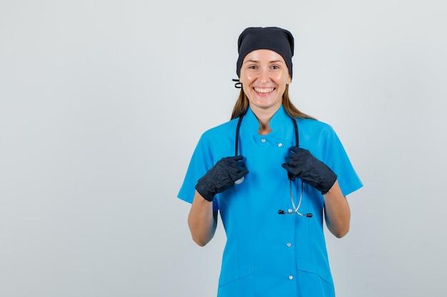 Femme médecin tenant la main sur le stéthoscope en uniforme, gants et à la joie