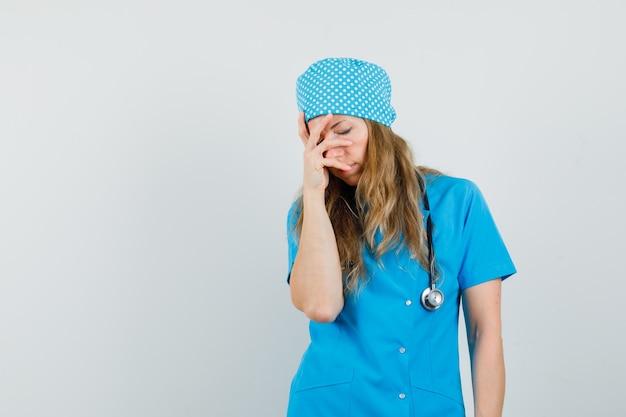 Femme médecin tenant la main sur le visage en uniforme bleu et l'air fatigué.