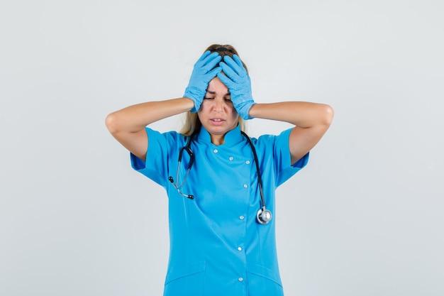 Femme médecin tenant les mains sur la tête en uniforme bleu, gants et à la recherche de désolé.