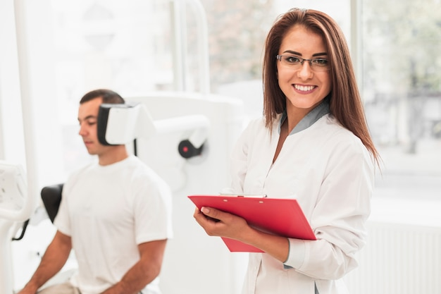 Femme médecin, tenant presse-papiers, et, regarder, photographe