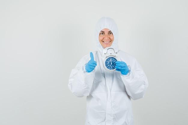 Femme médecin tenant un réveil avec le pouce vers le haut en combinaison de protection