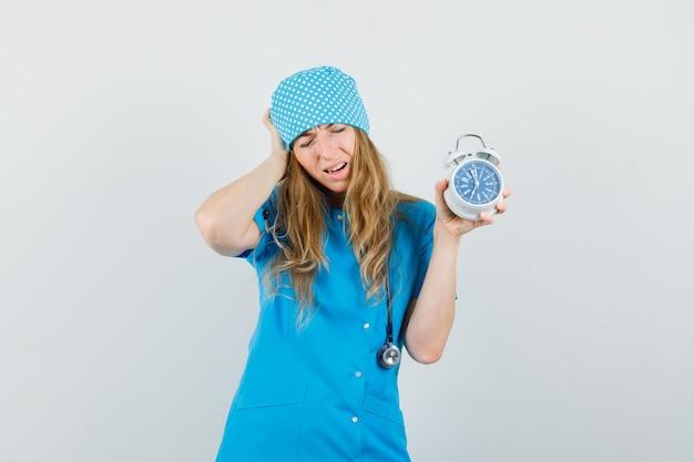 Femme médecin tenant un réveil en uniforme bleu et regardant oublieux.