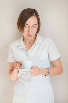 Femme médecin tenant une tasse de café