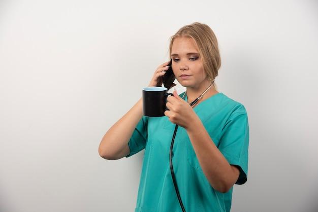 Femme médecin tenant le thé tout en parlant avec téléphone.