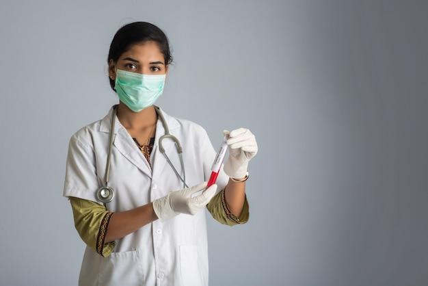 Femme médecin tenant un tube à essai avec un échantillon de sang pour le coronavirus ou l'analyse 2019-ncov.