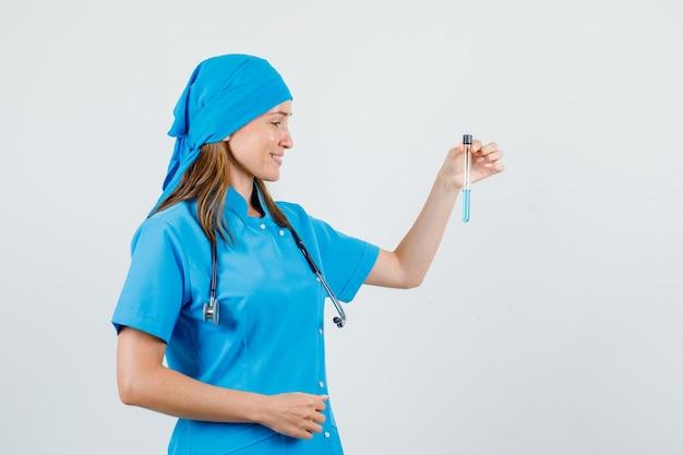 Femme médecin tenant le tube à essai et souriant en vue de face uniforme.