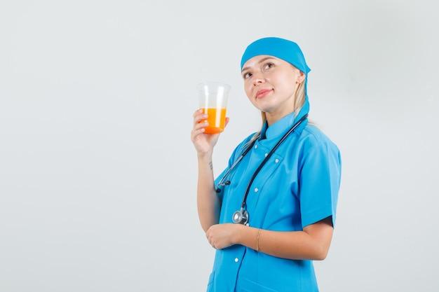 Femme médecin tenant un verre de jus tout en regardant en uniforme bleu et à la bonne humeur