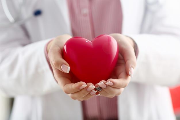 Femme médecin tenir dans les bras et couvrir jouet rouge