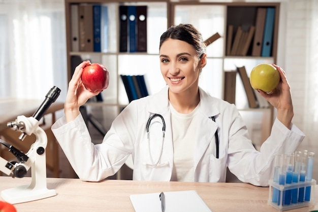 Femme médecin tient deux pommes dans les mains.