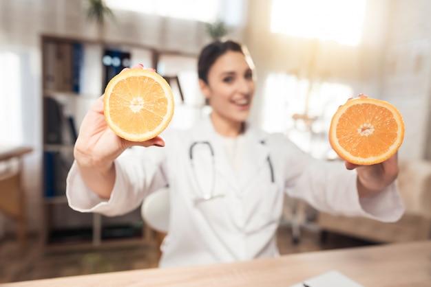 Femme médecin tient et montre des oranges