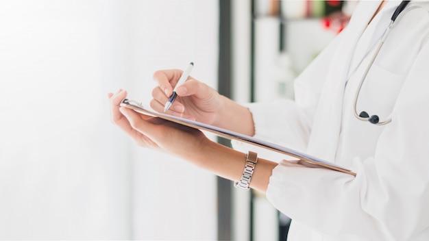 La femme médecin tient et rédige un rapport médical sur le traitement du patient à l'hôpital.