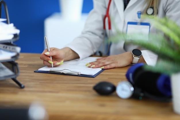 Femme médecin tient un stylo dans sa main et prend des notes dans des documents médicaux