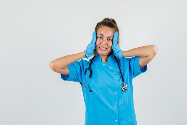 Femme médecin touchant le visage avec les mains en uniforme bleu