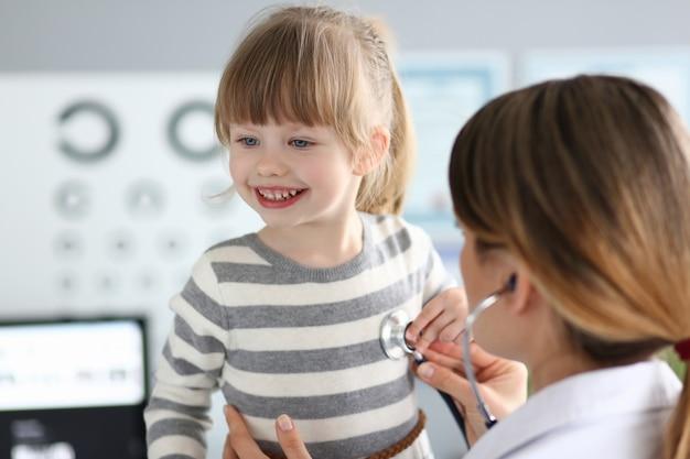 Femme médecin travaillant avec mignonne petite fille souriante à son bureau
