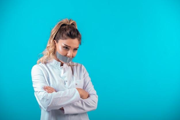 Femme médecin en uniforme blanc couvrant sa bouche et protestant.