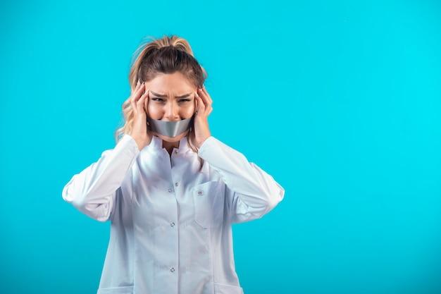 Femme médecin en uniforme blanc couvrant sa bouche et ses oreilles.