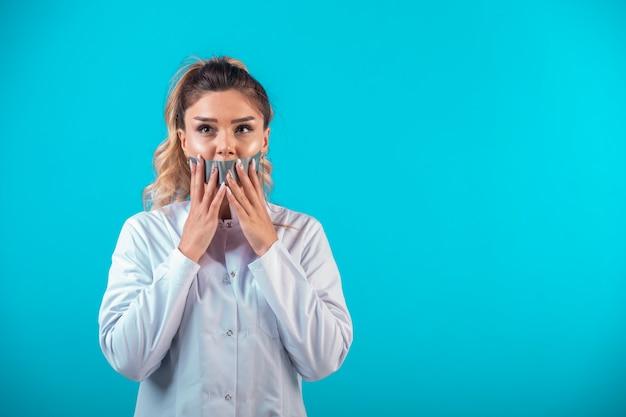 Femme médecin en uniforme blanc couvrant sa bouche.