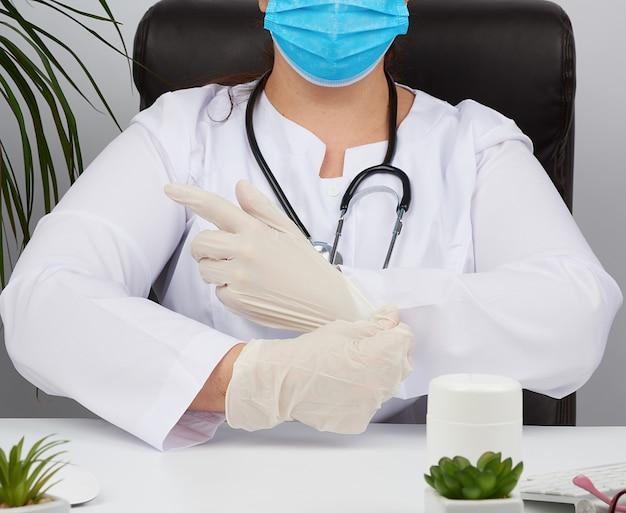 Femme médecin en uniforme blanc, masque médical jetable est assis sur une chaise à la table et met sur ses mains des gants en latex stériles blancs