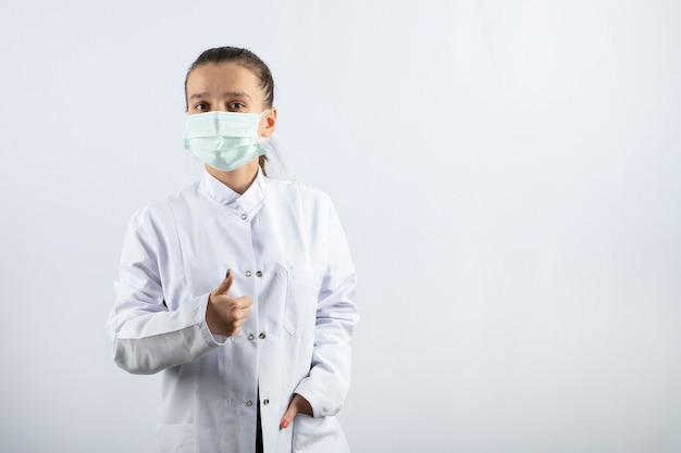 Femme médecin en uniforme blanc portant un masque médical montrant un pouce vers le haut