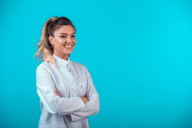 Femme médecin en uniforme blanc souriant.