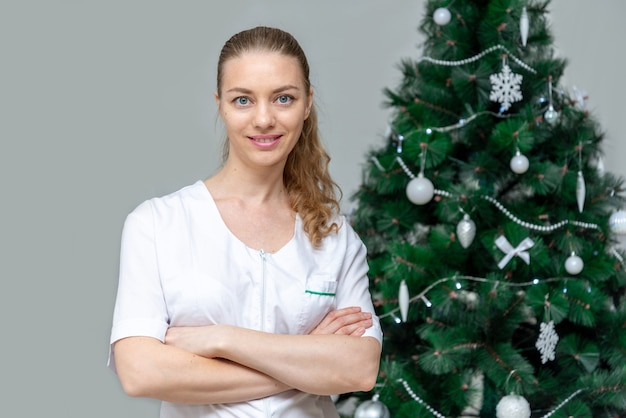 Une femme médecin en uniforme blanc sourit à côté d'un arbre de noël.