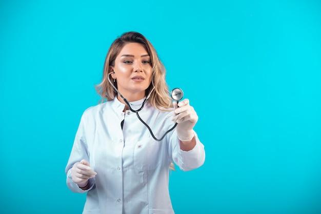 Femme médecin en uniforme blanc vérifiant avec stéthoscope et écoutant attentivement.