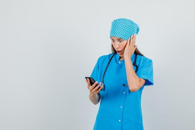 Femme médecin en uniforme bleu à l'aide de smartphone avec la main sur le visage et l'air choqué