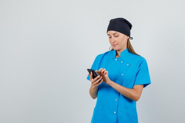 Femme médecin en uniforme bleu, chapeau noir à l'aide de smartphone et à occupé