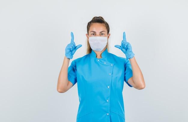 Femme médecin en uniforme bleu, masque, gants pointant vers le haut avec le geste du pistolet et à la confiance
