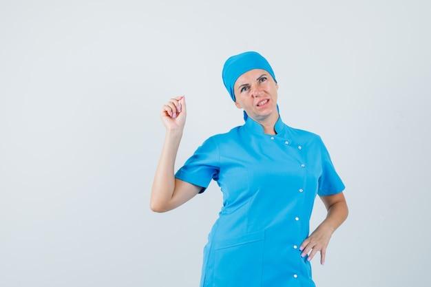 Femme médecin en uniforme bleu mesurant quelque chose de minuscule et regardant pensif, vue de face.