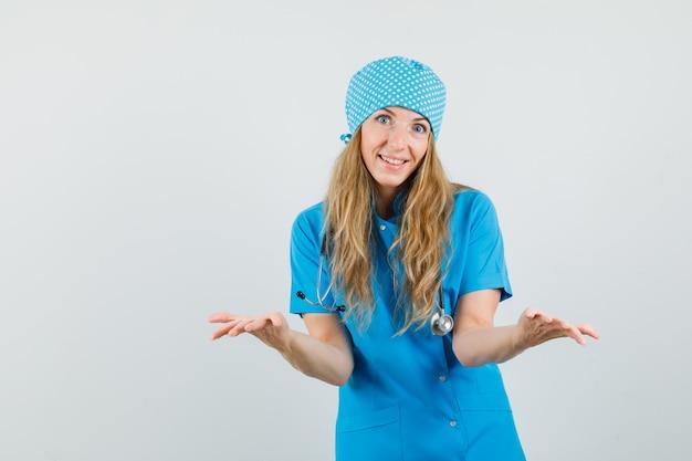 Femme médecin en uniforme bleu montrant un geste impuissant et à l'optimiste