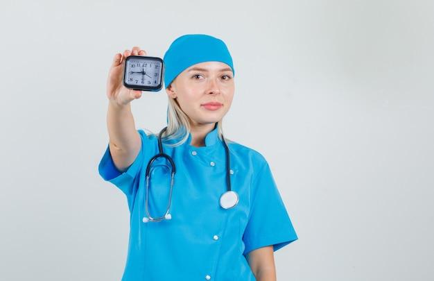 Femme médecin en uniforme bleu montrant horloge et souriant