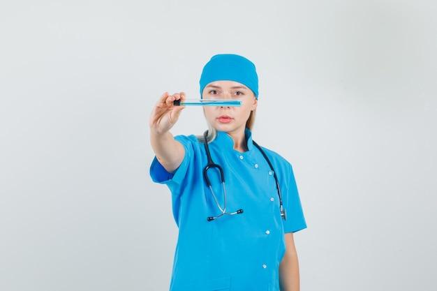 Femme médecin en uniforme bleu montrant tube à essai