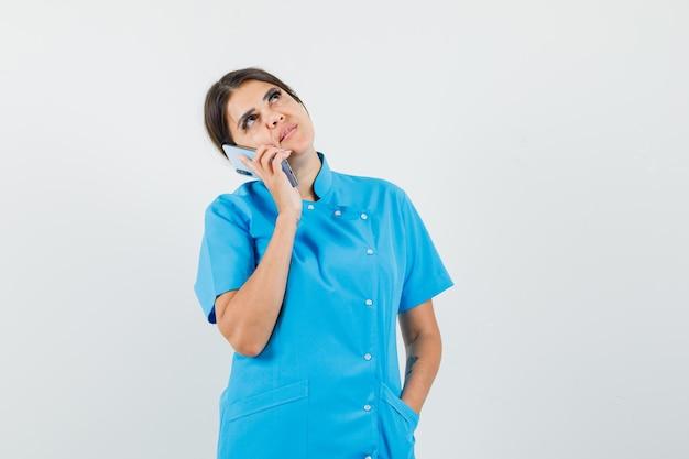 Femme médecin en uniforme bleu parlant au téléphone portable et regardant pensive