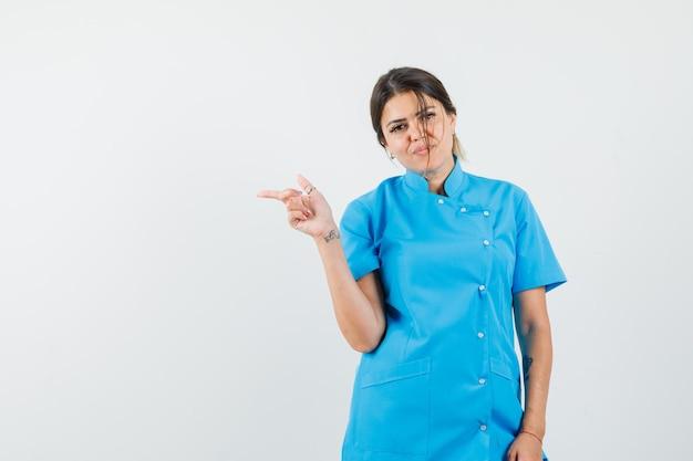Femme médecin en uniforme bleu pointant sur le côté et ayant l'air confiant