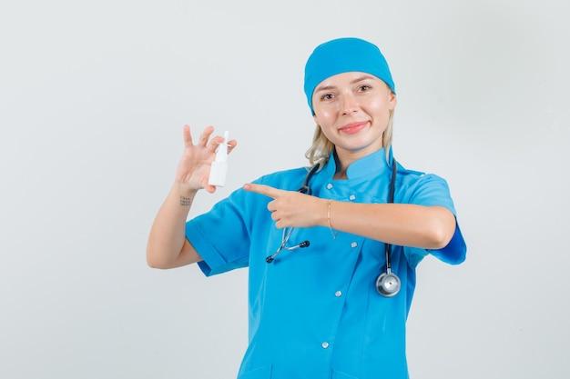 Femme médecin en uniforme bleu pointant le doigt sur la bouteille médicale et à la bonne humeur