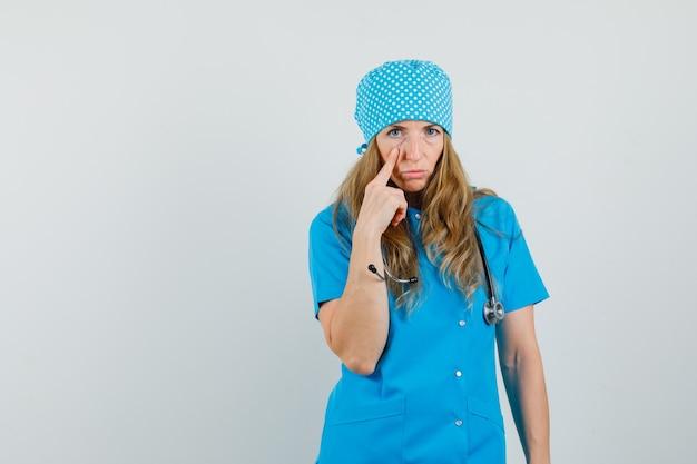 Femme médecin en uniforme bleu pointant sur sa paupière et l'air épuisé