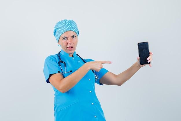 Femme médecin en uniforme bleu pointant sur le téléphone mobile et à la vue confuse, de face.