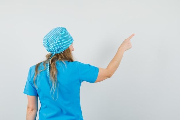 Femme médecin en uniforme bleu pointant vers l'extérieur et regardant focalisée, vue arrière.