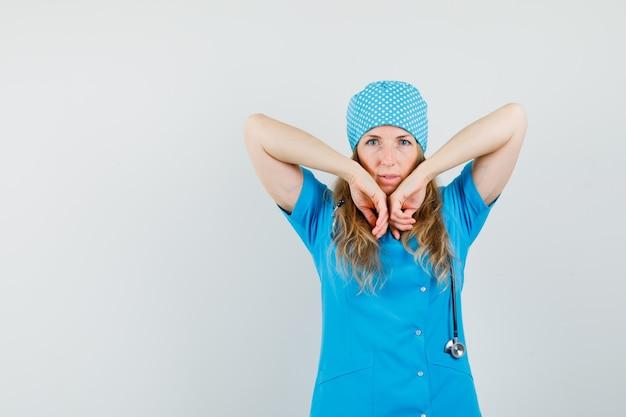 Femme médecin en uniforme bleu qui s'étend des coudes et à la confiance