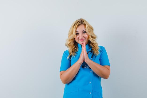 Femme médecin en uniforme bleu souhaitant quelque chose et à l'espace heureux pour le texte