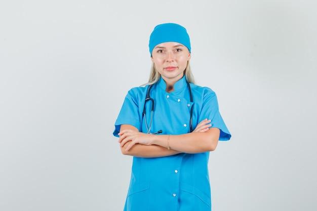 Femme médecin en uniforme bleu souriant avec les bras croisés et à la recherche d'espoir