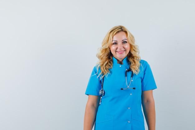 Femme médecin en uniforme bleu souriant et à la recherche d'un espace heureux pour le texte