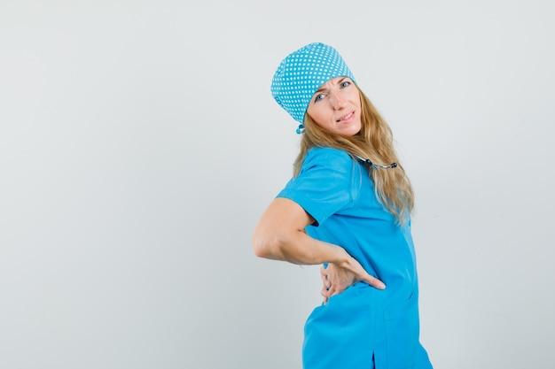 Femme médecin en uniforme bleu tenant les mains sur son dos et à la recherche de mal à l'aise.