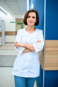 Femme médecin en uniforme debout dans le couloir de la clinique. médecin spécialiste en hôpital, laryngologiste ou oto-rhino-laryngologiste, gynécologue ou mammologue, chirurgien