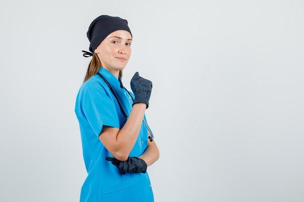 Femme médecin en uniforme, gants posant tout en gardant le poing levé et à la recherche de confiance.