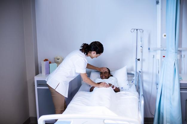 Femme médecin vérifiant la fièvre du patient dans le service