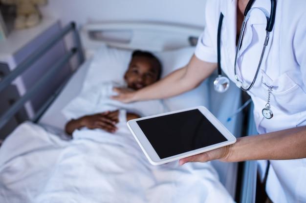Femme médecin vérifiant la fièvre du patient lors de la visite en salle