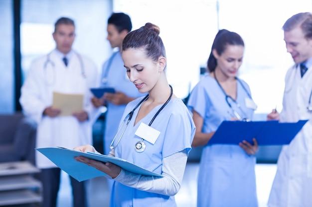 Femme médecin vérifiant le rapport médical pendant que ses collègues discutent