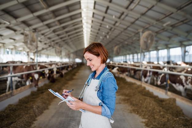 Une femme médecin vétérinaire travaillant dans une ferme journalière, dans l'industrie agricole.